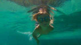 4x在他的手上计时逗人喜爱的小男孩潜水的慢动作射击入拿着两个小卵石的水池在水下 股票视频