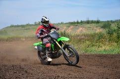 x比赛在一辆摩托车的MX车手在弯 图库摄影