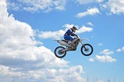 x站立在MX摩托车的比赛司机飞行在 库存图片