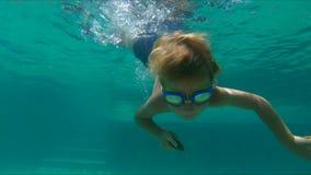 4x计时逗人喜爱的小男孩潜水入水池和敲的慢动作射击对小卵石在水下 股票录像