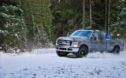 4x4 φορτηγό που παρασύρει στο δρόμο χειμερινού χιονιού στο δάσος Στοκ Εικόνα