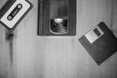 从90& x27的减速火箭的葡萄酒存储介质; s :录音磁带,录象带vhs,软盘在黑白的木背景 库存照片