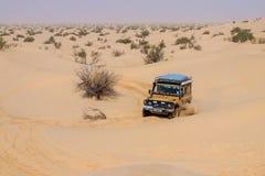 4X4车在撒哈拉大沙漠的沙丘附近驾驶 库存照片