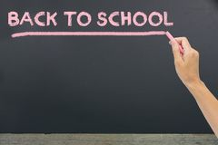 & x22;Back to school& x22; written by pink chalk on the black school chalk stock photography