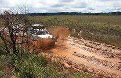 4x4 che guida attraverso il fango nel campo Immagine Stock Libera da Diritti