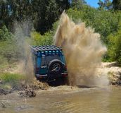 4x4 driving out a river bank. 4X4 suv driving out a sandy river bank with spray of sand Stock Photography