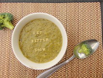 'Get better soon' written in vegetable soup with spoon. 'Get better soon' written on vegetable soup with spoon and vegetable next to it Royalty Free Stock Photography