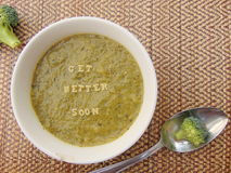 'Get better soon' written in vegetable soup with spoon. 'Get better soon' written on vegetable soup with spoon and vegetable next to it Royalty Free Stock Images