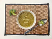 'Get better soon' written in vegetable soup with spoon. 'Get better soon' written on vegetable soup with spoon and vegetable next to it Stock Image