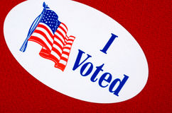 'I Voted' Sticker On Republican Red. Oval 'I Voted' sticker against a red or Republican colored background Royalty Free Stock Photo