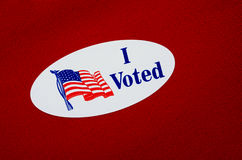 'I Voted' Sticker On Republican Red. Oval 'I Voted' sticker against a red or Republican colored background Royalty Free Stock Photos