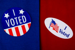 'I Voted' Stickers on Red And Blue. Two different kinds of 'I Voted' stickers on Democrat blue and Republican red. Divided America at election time Stock Photos