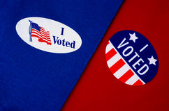 'I Voted' Stickers on Red And Blue. Two different kinds of 'I Voted' stickers on Democrat blue and Republican red. Divided America at election time Royalty Free Stock Photo