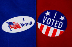 'I Voted' Stickers on Red And Blue. Two different kinds of 'I Voted' stickers on Democrat blue and Republican red. Divided America at election time Royalty Free Stock Photos