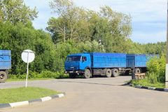 The & x22;Kamaz& x22; truck of blue color with a trailer is moving along, Royalty Free Stock Image