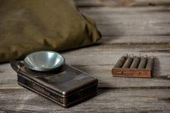 7,92 x 57 - las municiones rústicas, el poncho y la linterna vieja miente en el fondo de madera imagen de archivo