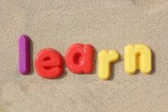 & x27; Learn& x27; skriftligt i plast- bokstäver på sanden Arkivfoton