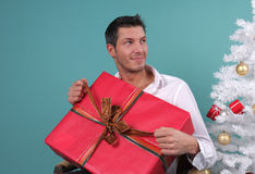 X-m,as present. Man opening christmas gift sitting on chair stock image