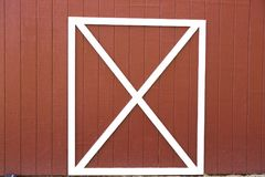 X Marks the Spot. Close up of the side of a red barn door with white cross trim Royalty Free Stock Photo