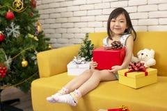 X-mas和假日概念 有礼物盒的愉快的儿童女孩 女孩在圣诞节盖帽手上出席包裹与金子纸和红色 免版税库存图片