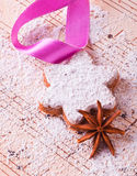 X-mas cookie. With a pink bow and icing sugar and one anise Royalty Free Stock Images