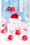 X mas decoration. Christmas decoration with red christmas balls and white letters of wood x mas and Santa Claus red hat in front of a winter window Stock Photos