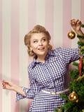 X-mas girl. Portrait of nice young woman hanging around christmas tree on x-mas  eve Stock Photo