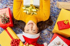 X-mas and holiday concept. Happy Female with gift box. Young women in christmas cap hands present wrapped with gold paper and red royalty free stock photography