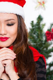 X-mas hope. Half-faced image of a young woman making a x-mas wish on the foreground Royalty Free Stock Photos