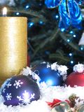 X-mas Ornaments. Shot of three Christmas balls and a burning candle. Christmas tree with blue lights used as a background stock photography