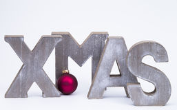 X-Mas with red christmas ball. Capital letters forming the word xmas with red christmas ball over white stock images