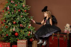 X-mas, winter vacation and people concept - little girl in black angel costume sits on a trunk near a Christmas tree and looks at Stock Images