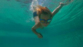 4x mide el tiempo del tiro a cámara lenta de un salto lindo del niño pequeño en la piscina que sostiene dos guijarros debajo del  almacen de video
