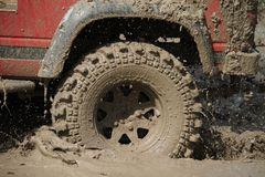 4x4Offroad car - 4wd vehicle is driving uphill out of water and Stock Photos