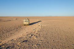 4x4 offroad vehicle driving in empty flat and rocky Namib Desert of Angola. Vintage 4x4 offroad vehicle driving in empty flat and rocky Namib Desert of Angola Stock Photo
