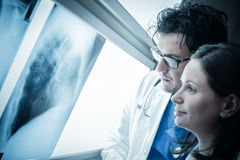 X-ray films. Two yound doctors examining a x-ray film at the diaphanoscope Royalty Free Stock Photography
