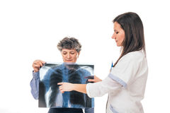 X-ray's examination. Young doctor is analyzing lungs x-ray while patient holding it - isolated on white stock photo