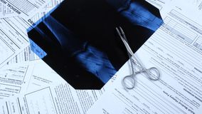X-ray with surgical clamp on medical papers, rotation. X-ray with surgical clamp on different medical papers, rotation stock footage