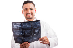X-Ray technician at work. Young Hispanic radiographer examining some x-rays and smiling against a white background Stock Photography