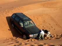 4x4 stuck in sand. Two people trying to rescue stuck 4x4 stock photos