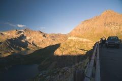 4x4 SUV在路停放了在意大利阿尔卑斯的全景点 看看法的一个人 在日落,被定调子的imag的五颜六色的天空 库存图片