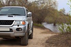 4x4 SUV auf einer Straße nahe einem Fluss Lizenzfreie Stockfotografie