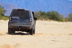4x4 0n sand. 4X4 suv on dusty sand outdoors driving Royalty Free Stock Photo
