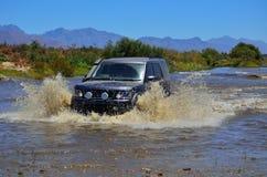 4x4 SUV que cruza um rio Fotografia de Stock