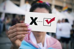 X for the third gender category. Closeup of a young person, wrapped in a transgender pride flag, holding a piece of paper with a check mark on an X letter for stock photo