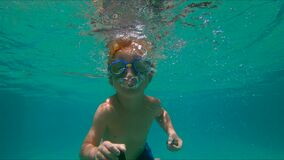 4x times slowmotion shot of a cute little boy diving into pool holding two pebbles under water in his hands.  stock video footage