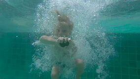 8x times slowmotion shot of a cute little boy diving into pool holding two pebbles under water in his hands.  stock footage
