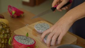 2x times Slowmotion shot of a young woman cutting the dragon fruit into cubes and lots of tropical fruits lay on a table.  stock footage