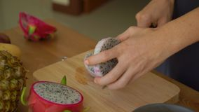4x times Slowmotion shot of a young woman cutting the dragon fruit into cubes and lots of tropical fruits lay on a table.  stock video