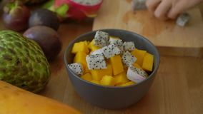 4x times Slowmotion shot of a young woman putting the dragon fruit cubes into a grey ceramic bowl and lots of tropical. Fruits lay on a table stock footage